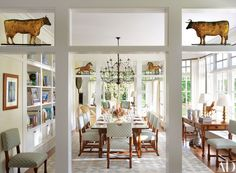 The dining room was opened up to the den, at rear, and the living room. Dillingham & Company carved dog under writing table from Notus. Lee Calicchio chandelier. Marvin Alexander brass lamps. Bergamo drapery fabric. Blue chair check, Lee Jofa. Elizabeth Eakins rug | archdigest.com