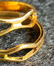 ANILLOS NUDILLO DORADOS: Anillos de nudillo, en acrílico con baño en oro de 18 k, color dorado. Ajustables. 2 Piezas.