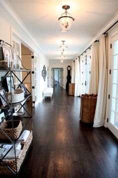 wide open hallway, white on white, black hardware, natural textures, matching lighting, french doors