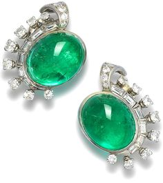A pair of emerald and diamond ear clips, by Mauboussin.     Each set with an oval emerald cabochon, within a half border of stylised scroll set with baguette and round brilliant-cut diamonds, mounted in 18k white gold, the emeralds estimated to weigh approximately 28.00 carats in total, the diamonds estimated to weigh approximately 3.00 carats in total, signed 'Mauboussin, Paris', French control marks, earring length 2.9cm. Via Bonhams.