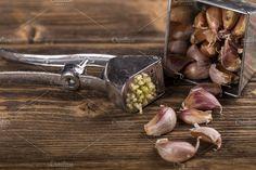 #Garlic  Garlic and garlic press on rustic wooden board