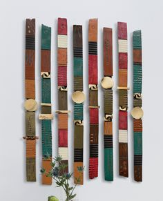 Story Sticks Ceramic Wall Art Created by Rhonda Cearlock A variety of textured, pit-fired, and acrylic-painted clay shapes are combined to create colorful, rhythmic sculptures for your wall. Mounted on wood backing. Ready to hang. Each 34″H, 2″W, 1″D