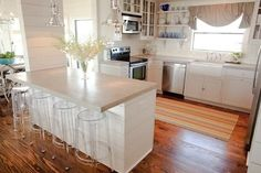 Cool kitchen...love the wood floor, stained concrete countertops and acrylic stools!