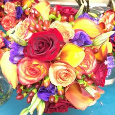 Wedding bouquet of yellow calla lilies, mango calla lilies, red roses, High Magic roses, purple lissianthus, and red hypericum berries
