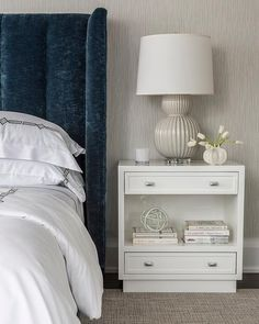 White and blue bedroom boasts a dark blue velvet art deco bed dressed in white and gray bedding placed next to white lacquer open nightstand and a gray rippled lamp, Bungalow 5 Meridian Table Lamps.