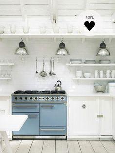 Witte keuken met blauw/grijs fornuis en industriële lampen.