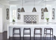 """Kitchen. White Kitchen with custom designed backsplash, dark hardwood floors and large island. The pendants are by """"Visual Comfort, Goodman Small Hanging Lights"""".  Kitchen Hardware: The hardware is """"Top Knobs Square Bar Pull M1286"""".  The counter stools were custom-made for the clients. The backsplash is a customized natural stone mosaic available through """"Famosa Tile"""". Countertop is """"Calacatta Marble"""".  #Kitchen #WhiteKitchen"""