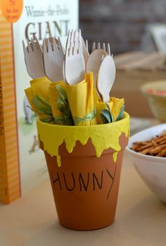 Adorable way to showcase flatware at a Winnie the Pooh party - just a terra cot pot dipped in some paint!