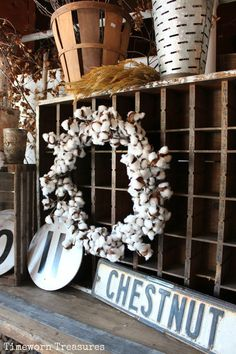 Cotton wreath on an old divided wooden work cubby - We love the writing detail on the wood. This piece, along with the cotton wreath, would be a great addition to your wall - Simple, fresh, and unique. Also in this picture - vintage wooden round numbers, vintage black and white metal street sign, olive buckets, old bushel baskets, wheat, and more.