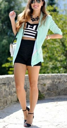 Black high waisted shorts with a bright cardigan and striped bustier crop top | Street Style