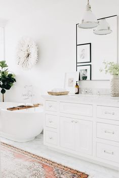 You'll rush home to a nice warm bath in this gorgeous white bathroom featuring an oval soaking bathtub fitted with a polished nickel vintage tub filler and placed beside a fiddle leaf fig plant and beneath a white juju hat. Ikea Bathroom Vanity, Bathroom Rugs, White Bathroom, Carpet In Bathroom, Master Bathroom, Vanity Mirrors, Bathroom Showers, Ensuite Bathrooms, Bathroom Small