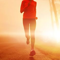 A woman running on a road with the sun behind her.