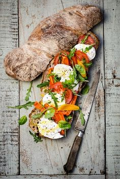 A sandwich with mozzarella, tomatoes, rocket and basil (Italy)