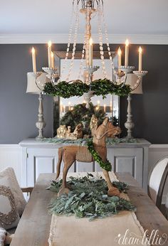 These lamps and vintage style wooden horse from @homegoods adds a rustic feel to this otherwise more elegant feeling dining room with it's oversized chandelier and dark gray walls. (sponsored pin)
