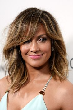 Not sure if you want to commit to full on bangs? Try a tousled sideswept look like JLo.