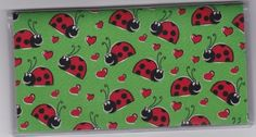 """Happy Ladybugs and Hearts on Green Checkbook Cover by Tickled Pink Boutique. $5.00. The sturdy clear VINYL COVER encases a fabric bonded design. Measuring 6 1/4"""" x 3 1/4"""",  the cover fits all standard bank checkbooks and banking registers.  All checkbook covers come with a register flap and a duplicate check flap  just like the bank, only flashier.  These checkbook covers are a great alternative to the expensive covers offered by banks and online check companies."""