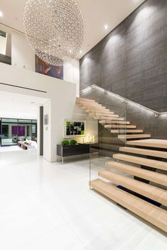 Wood stairs with a glass safety rail lead you upstairs and give you a great view of the 6 ft Moooi chandelier.