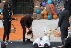 "US President Barack Obama and First Lady Michelle Obama greet a young child dressed as the Pope and riding in a ""Popemobile"" as he hands out treats to children trick-or-treating for Halloween on the South Lawn of the White House in Washington, DC, October 30, 2015. AFP PHOTO / SAUL LOEB        (Photo credit should read SAUL LOEB/AFP/Getty Images)"