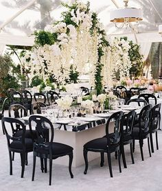 Orchids with hanging greens were draped across the clear top tent. Our White and Gold Tuxedo Chandeliers added a sophisticated element to the ceiling design Guests dined at our mirrored tables on our Black Madrid chairs. Creative Partners: Planning: @MindyWeiss Floral and Design: @MarksGarden Venue: #GullsNestWay Furnishings and Design: @RevelryRomina for #RevelryEventDesign Photography: @EricKelley