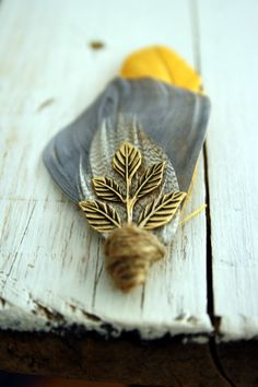 Boutonniere- deep golden yellow coque tail feathers, charcoal grey goose feathers, mottled brown plumes and an antiqued brass Grecian leaf, all wrapped up in rustic twine.
