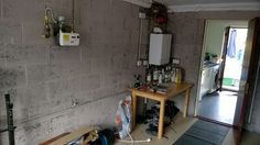 Showing the bare wall with boiler and gas meter to be incorporated in the shelf and cabinet construction