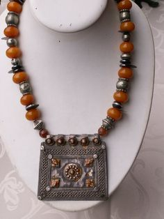 by Anne Marie | An old square shaped silver pendant with traces of orange enamel from Central Asia. The necklace itself is strung with wonderful old silver beads from India, man made amber beads, ebony beads with silver inlay, hematite disks and a few ancient coins with arabic inscription | BeadArt Austria Designs