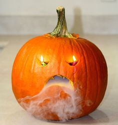 Scary and spooky jack-o'-lantern with dry ice fog and candles for eyes.