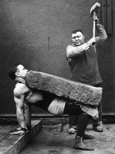 Circus World: Man crushes a block placed on the stomach of a strongman. (1930)