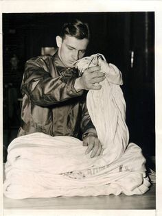 1941- Soldier of the 501st Parachute Battalion folding his parachute at Fort Benning, Georgia.