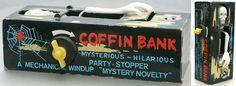 Coffin Bank - Griezel Spaarpot. Leg er een muntstuk op en het skelet grijpt je muntstuk en trekt het in zijn doodskist. Er hoort nog een zwart doekje overheen, dat mist hier echter.