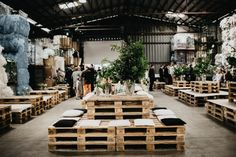 Wooden palette tables, black and white pillows, lush green centerpieces | Photo by Couple of Prague