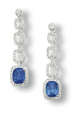 A PAIR OF SAPPHIRE AND DIAMOND EAR PENDANTS  Each suspending a cushion-shaped sapphire within a pavé-set diamond surround, to the line of pavé-set diamond links and brilliant-cut diamond surmount, mounted in platinum, 4.7 cm long