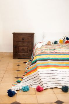 The Moroccan Pom Pom Blanket is a beautiful accessory for the Bohemian style home. It can be used as a blanket, coverlet for the bed or throw for the sofa. Made of 100% wool or 100% cotton, it is handcrafted in our small workshop in the Medina of Marrakech.  - 100% Cotton - Handmade in Marrakech, Morocco  This item is available in 4 sizes. SIZES  Small: 59 x 59 niches (1.5 m x 1.5 m) Medium: 59 x 98 inches (1.5 m x 2.4 m) Large: 78 x 118 inches (2 m x 3 m) Extra-Large: 94 x 118 inches (2.4…