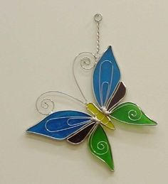 Blue and Green Stained Glass Butterfly Suncatcher by In the Garden and More. $24.95. Handmade by skilled artisans. Will sparkle and shine. Colorful and unique. Hang from a hook or nail or suction cup. Great gift any time of the year. This beautiful hand-cut and hand-crafted stained glass butterfly suncatcher is completely made by hand by skilled artisans who have a love for detail and the art of stained glass beauty. Each piece is carefully hand cut and soldered ...