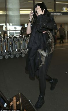 First class fashion: For her air travel Kylie wore long all black, from her long leggings ...