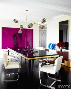 Oversized magenta artwork in modern dining space with black table, white chairs, and Sputnik light fixture