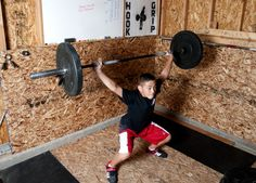 Bryant Phelps goes lifts during a workout in the garage of his Providence, Utah, home. The 13-year-old recently competed in a national weightlifting competition an took home several second-place awards. (Photo by John Zsiray)