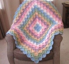 This Rainbow Bavarian Crochet Blanket will brighten up any home, and you can even work it up yourself! Using a Bavarian stitch will require intermediate crocheting skills, but it's a free pattern, so give this delightful blanket a try. #crochetafghans