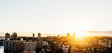 Panoramic view on Australian city at sunrise. Architecture gallery by Trent Lanz for Stocksy United - Royalty-Free Stock Photos. australia, bay, beautiful, bright, building, calm, city, cityscape, copy space, harbour, holiday, horizon, horizontal, morning, mountain, new day, nobody, outdoors, panorama, peaceful, picturesque, resort, roof top, scenery, scenic, seascape, sky, sun, sunlight, sunrise, travel, travelling, view