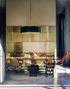 In the dining room, the table, designed by Vincenzo De Cotiis, is surrounded by wooden armchairs 1950, a stool 1970 and vintage garden furniture.  Concrete walls are clad with recycled fiberglass panels.