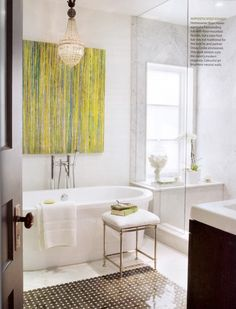 Abstract art pops in white bath; chandelier over bath tub
