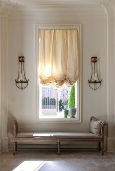 love the bench below the window and the symetry of the sconces on either side of the window
