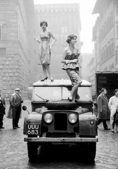 Two girl models standing on the roof of a Land Rover in Florence, Italy, 1958