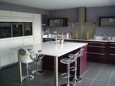 cuisine ouverte haute de gamme, plan de travail et ilot central en qartz. la cuisne a un accès direct à la