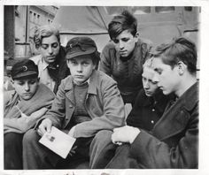 1945- German boys, all members of the Hitler Youth, captured by the U.S. 1st Army. The boys were being trained as glider pilots and anti-aircraft gunners. Each boy possessed a soldiers pay book, which one of them displays.