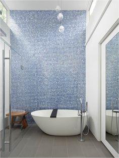 wall of mosaic tile, freestanding tub, frameless shower