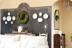 Love this chalkboard wall with curved top, white plates, wreath, sculptural cow head & swirling chalk artwork.
