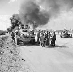 THE BRITISH ARMY IN NORTH AFRICA Local people gather round Humber armoured cars in Benghazi while in the background smoke can be seen filling the sky from a burning oil tanker, November Knight (Lieut): No. 1 Army Film & Photographic Unit © IWM (E Oil Tanker, Afrika Korps, Tank Destroyer, Armored Fighting Vehicle, Ww2 Tanks, British Army, British Tanks, Armored Vehicles, North Africa