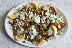 Greek Fries doused with all sorts of fresh herbs, drizzled with tzatziki, fresh lemon juice and a bit of feta makes for the perfect game day snack