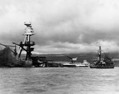Battle ship Arizona at pearl Harbor, December 1941. The photo was taken shortly after the battleship was bombed and destroyed during the surprise attack by Japanese forces, December 7, 1941. The vessel at right is a rescue tug. Flag still flying the ship is resting on the bottom of the ocean with decks flooded. (AP Photo
